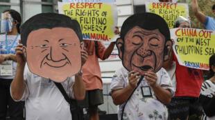 Ảnh minh họa: Người Philippines biểu tình trước lãnh sự quán Trung Quốc tại Manila ngày 07/05/2021 đòi Bắc Kinh rút ra khỏi vùng Biển Đông mà Philippines tuyên bố chủ quyền. Họ đeo mặt nạ của tổng thống Philippines Rodrigo Duterte và chủ tịch Trung Quốc Tập Cận Bình. Ông Duterte bị cáo buộc là đã thần phục Bắc Kinh.