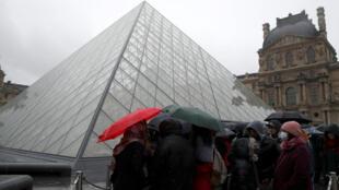 3月1日,在盧浮宮金字塔旁冒着雨排隊的遊客非常失望。盧浮宮突然關閉了。
