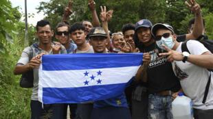 Un groupe de migrants honduriens, qui font partie de la caravane qui se dirige vers les États-Unis, agite un drapeau de la pays, près d'Izabal au Guatemala, le 2 octobre 2020.