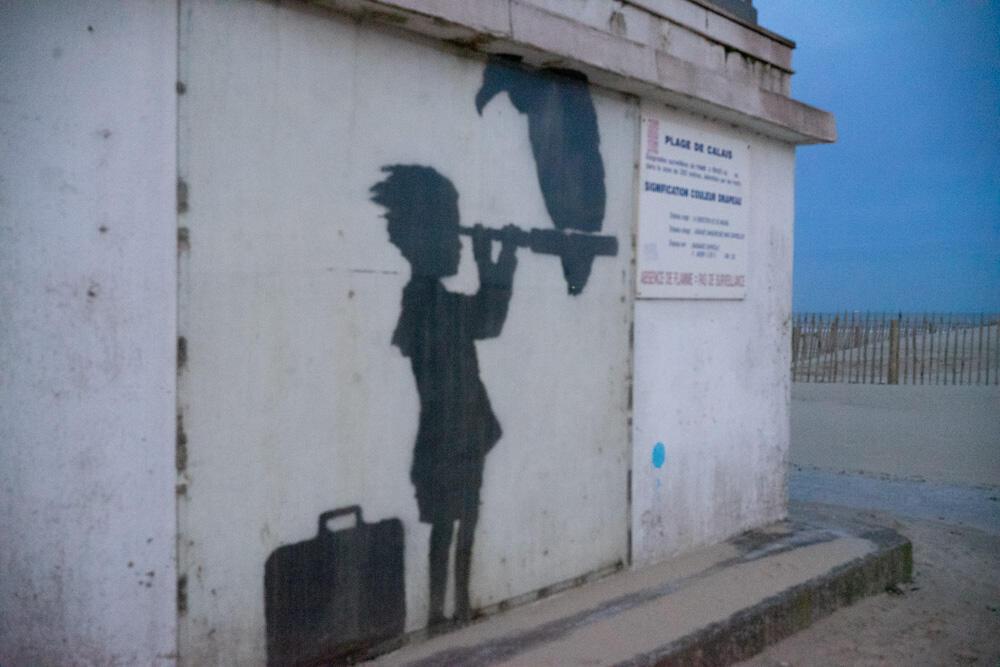 Um grafite de Banksy em Calais, norte da França, faz referência a clandestinos que tentam alcançar a Inglaterra pelo mar. A obra está protegida por uma tela de acrílico. Calais, 16/03/2020.