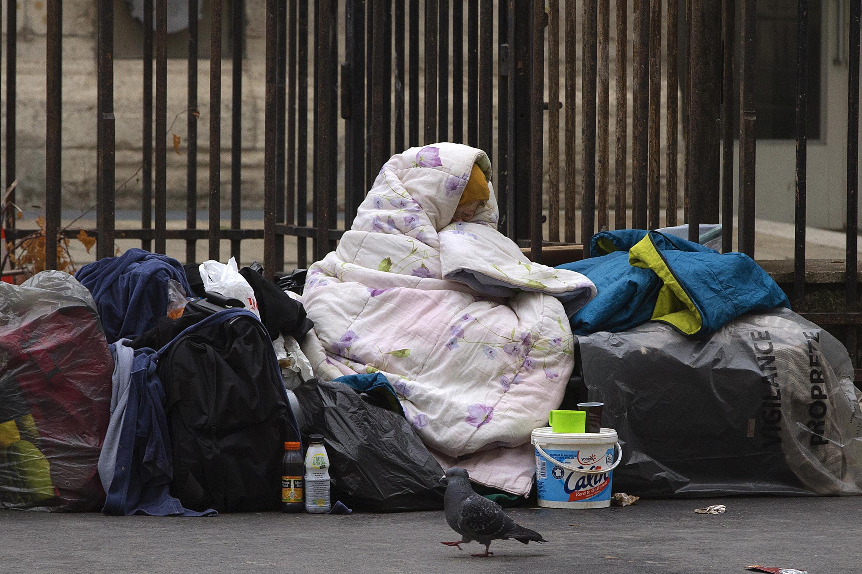 Une femme sous une couverture dans une rue de Paris.