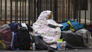 Une femme sous une couverture, dans une rue de Paris.