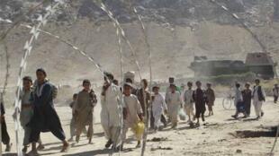 Afghan schoolchildren walk past an Afghan military compound  in Kandahar province