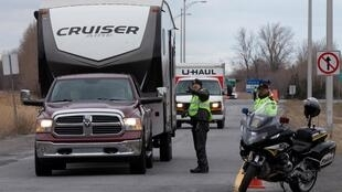 Des agents de police du Québec contrôlent les conducteurs de la province de l'Ontario voisin afin d'appliquer les restrictions liées au coronavirus près de Saint-Zotique. Québec, le 1er avril 2020.