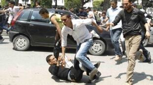 Des manifestants antigouvernementaux fuient la police à Tunis, le 6 mai 2011.