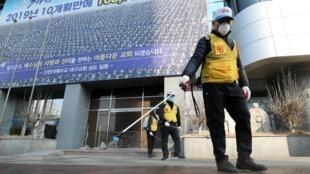 Des employés désinfectent les alentours des locaux de la secte «l'Église Shincheonji de Jésus», d'inspiration chrétienne, à Daegu, le 20 février 2020.