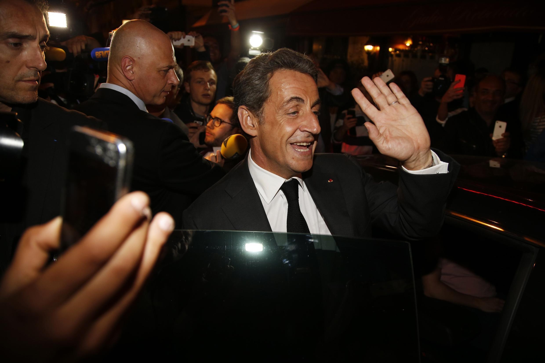 O ex-presidente francês Nicolas Sarkozy na saída de um restaurante, após conceder entrevista à televisão.