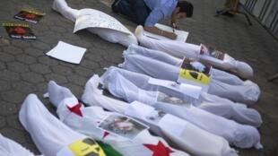 Un homme se prépare à manifester devant l'immeuble des Nations unies à New York, le 21 août 2013. Des mannequins enveloppés dans des linceuls évoquent les milliers de morts en Syrie.