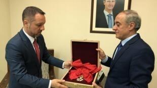 Đại diện bộ Ngoại Giao Syria (T), qua sứ quán Rumani làm trung gian, trả lại Paris huy chương Bắc Đẩu Bội Tinh mà Pháp đã trao cho tổng thống Bachar Al Assad.