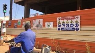 Un homme à moto passe devant des affiches de campagne, à deux jours de la présidentielle au Burkina Faso, le 20 novembre 2020.