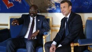 Georges Weah e Emmanuel Macron no Palácio do Eliseu em Paris a 21 de Fevereiro de 2018.