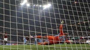 Dan wasan AC Milan Mario Balotelli a lokacin da Pepe Reina mai tsaron gidan Napoli ya kabe kwallon shi a bugun daga kai sai mai tsaron gida