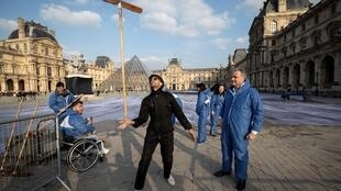 French artist JR poses with volunteers during preparation works of his installation in the main courtyard Cour Napoleon of the Louvre Museum in Paris on 27 March, 2019.