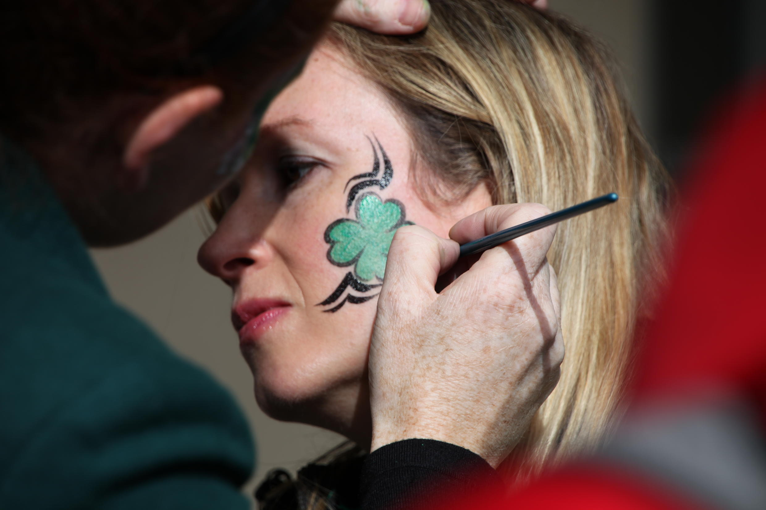 This woman has a shamrock painted on her face -  the three-leaved plant that Saint Patrick is said to have used as a symbol for the Holy Trinity