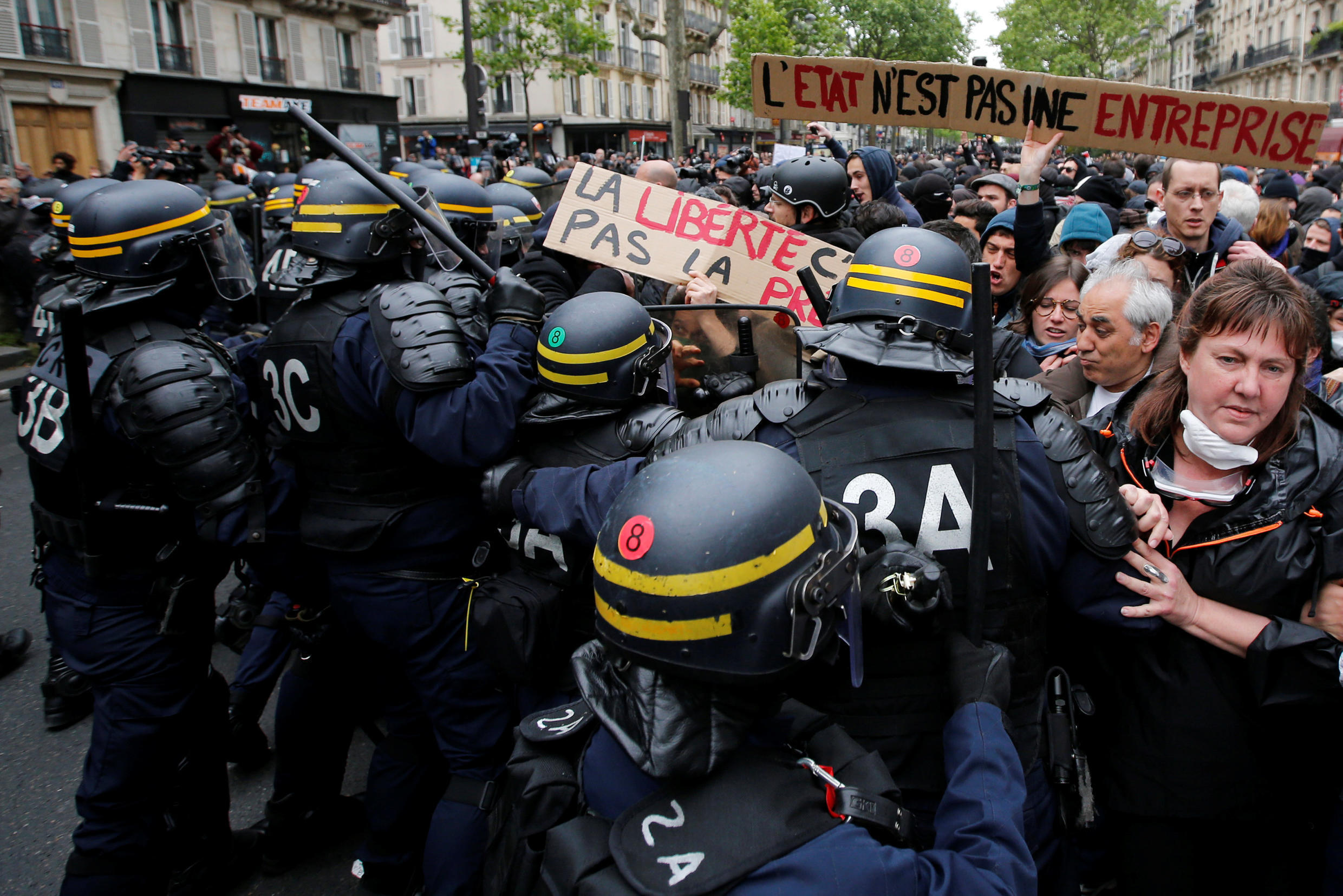 """French riot police surround demonstrators who hold a placard with the message, """"The State is not an Company"""", the day after the country went to the polls, in Paris, France, May 8, 2017."""