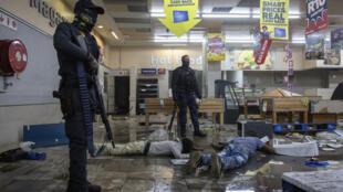 Des policiers se tenant devant des suspects interpellés dans un magasin pillé à Johannesburg.