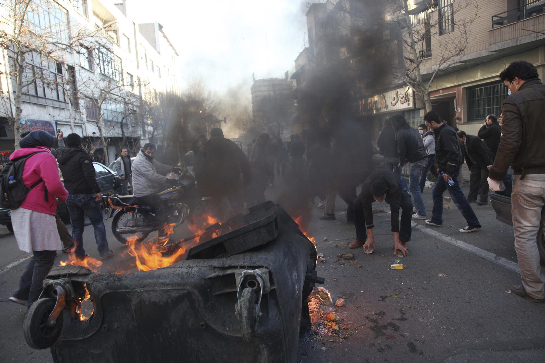 Los manifestantes queman un tacho de basura cerca de la Plaza  Azadi, en Teherán.