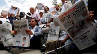 Люди читают газету Cumhuriyet на акции в поддержку арестованных журналистов, Стамбул, 28 июля 2017 года.