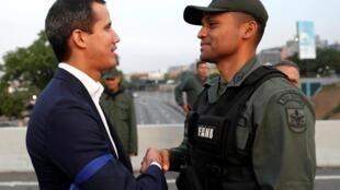Aperto de mãos entre Juan Guaidó e um militar da Força Armada Nacional Bolivariana (FANB), em 30 de abril de 2019.
