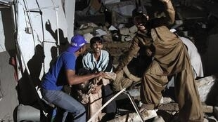 Rescue workers and volunteers ask for help as they pull the injured from the rubble at the site of the bomb attack in Karachi