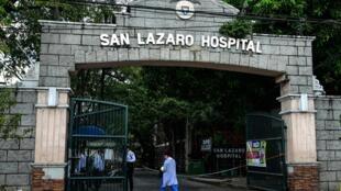 Des personnes portant des masques passent devant les portes principales de l'hôpital San Lazaro à Manille le 2 février 2020.
