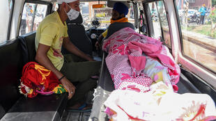 Un hombre está sentado al lado un fallecido por beber alcohol de contrabando en Tarn Taran (Punjab, nordeste de India), 2 de agosto de 2020