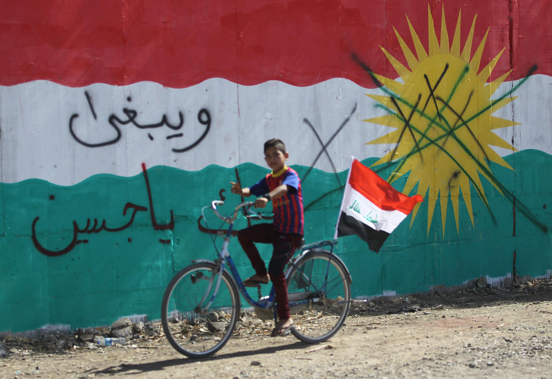 Un enfant passe à vélo devant un mur sur lequel on peut voir le drapeau irakien, le 17 octobre 2017 à Dibs, à l'ouest de Kirkouk.