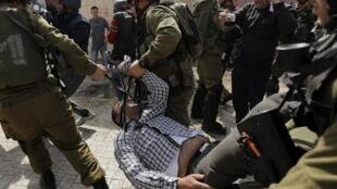 Soldados israelíes arrastran a un palestino que protestaba por el cierre de la calle Shuhada a los palestinos, Hebrón, 21 de febrero de 2014.