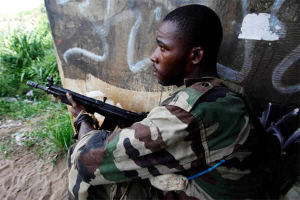 A soldier loyal to Alassane Ouattara holds a position along a road on 4 April, 2011 as fighting flared across Abidjan