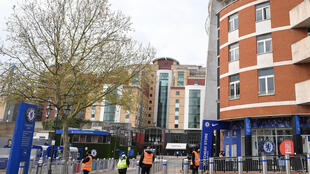 Security guards stand with stewards outside Chelsea's Stamford Bridge stadium