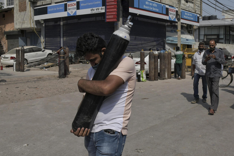 Un hombre camina con una bombona llena mientras los familiares de los pacientes esperan en la cola para llenar sus bombonas de oxígeno en la zona de Mayapuri de Nueva Delhi, India, el lunes 3 de mayo de 2021.