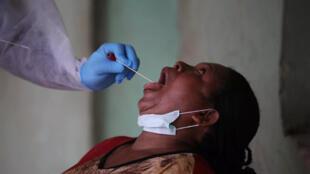 Wani jami'in kiwon lafiya a birnin Abuja dake Najeriya, yayin yiwa wata mata gwajin cutar coronavirus.