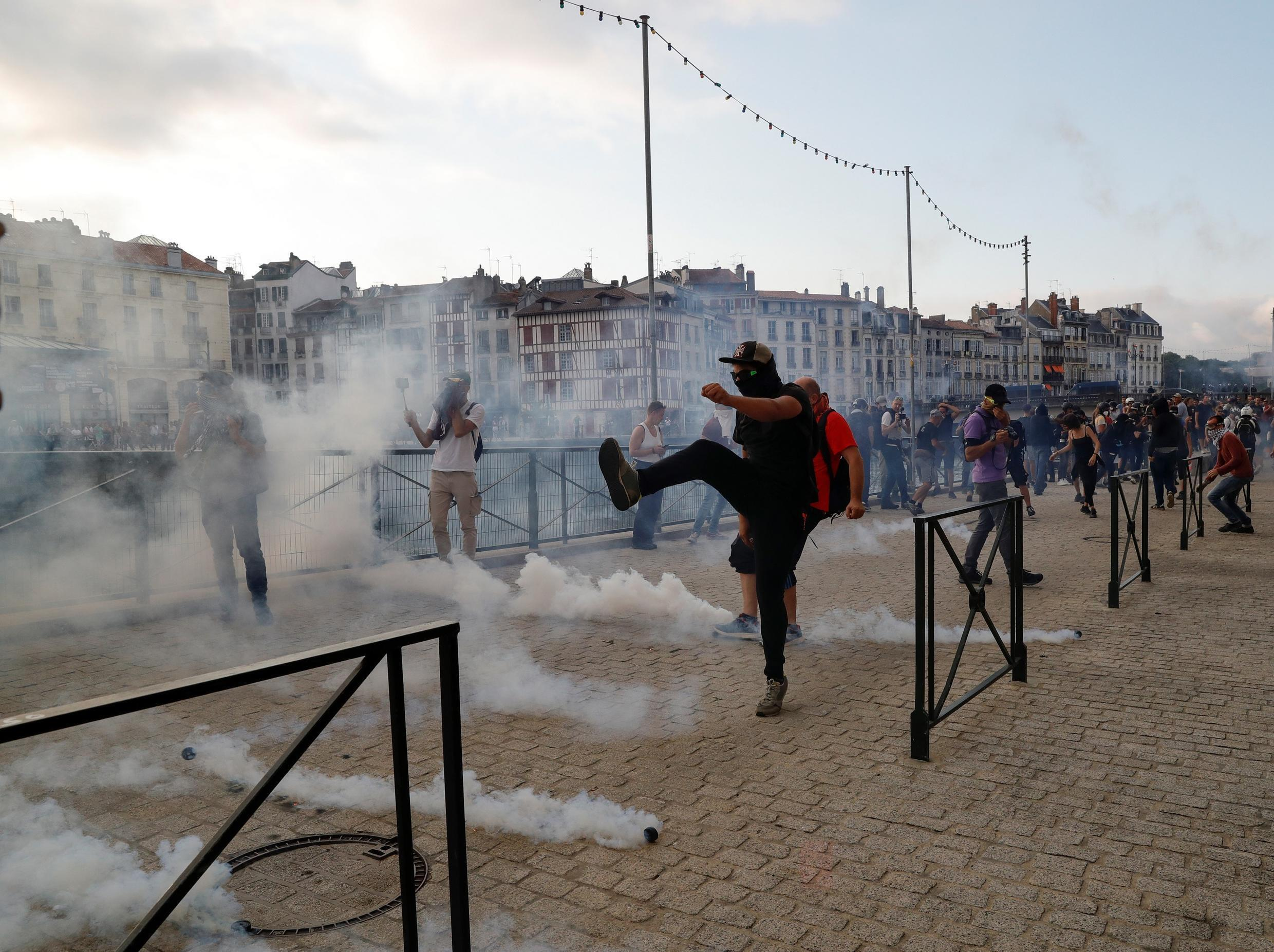 A protester kicks a tear gas grenade in Bayonne on 24 August 2019.