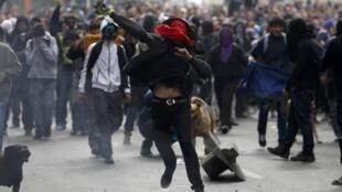 Estudante atira garrafa de tinta na polícia chilena durante manifestação pela reforma da educação nesta quinta-feira, 11 de abril, em Santiago, no Chile.