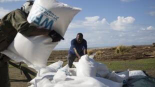 Des Haïtiens déchargent des sacs du Programme alimentaire mondial.