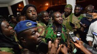 Issiaka Ouattara (c), porte-parole des soldats insurgés, parle aux journalistes après les négociations avec le ministre chargé de la Défense, à Bouaké, le 7 janvier 2017.