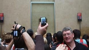 Tourists scrablle to snap the Mona Lisa in the Louvre