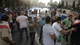 Gases lacrimógenos contra los manifestantes que intentan entrar en la sede del gobierno este domingo en Beirut