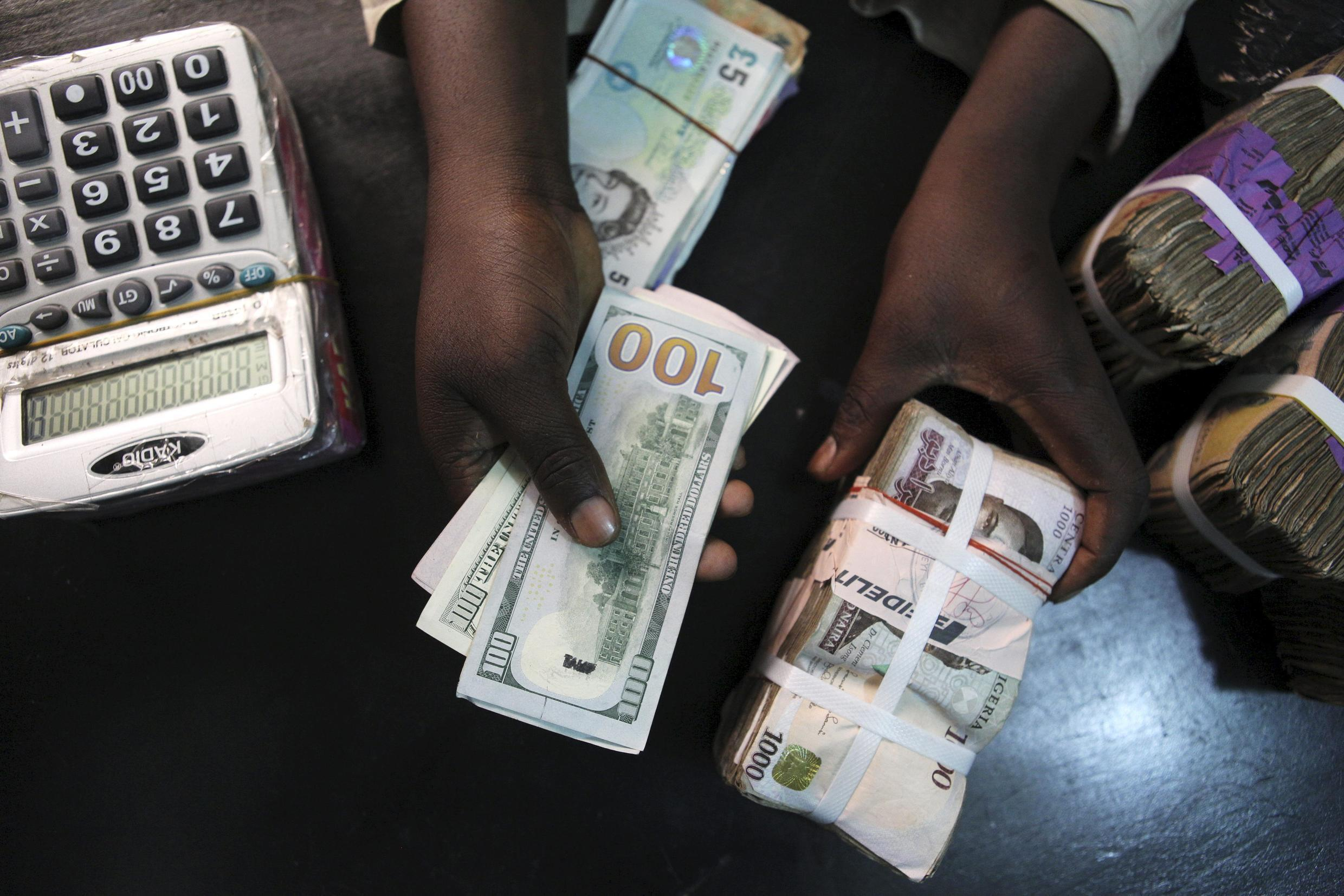 A trader changes dollars for Naira at a currency exchange store in Lagos, Nigeria in this February 12, 2015