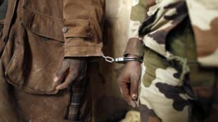 Un prisonnier menotté à un gendarme malien dans le centre de Tombouctou, le 1er février 2013.