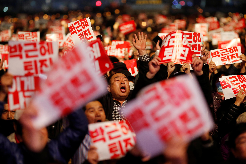Manifestantes coreanos exigem a renúncia da presidente Park Geun-Hye.