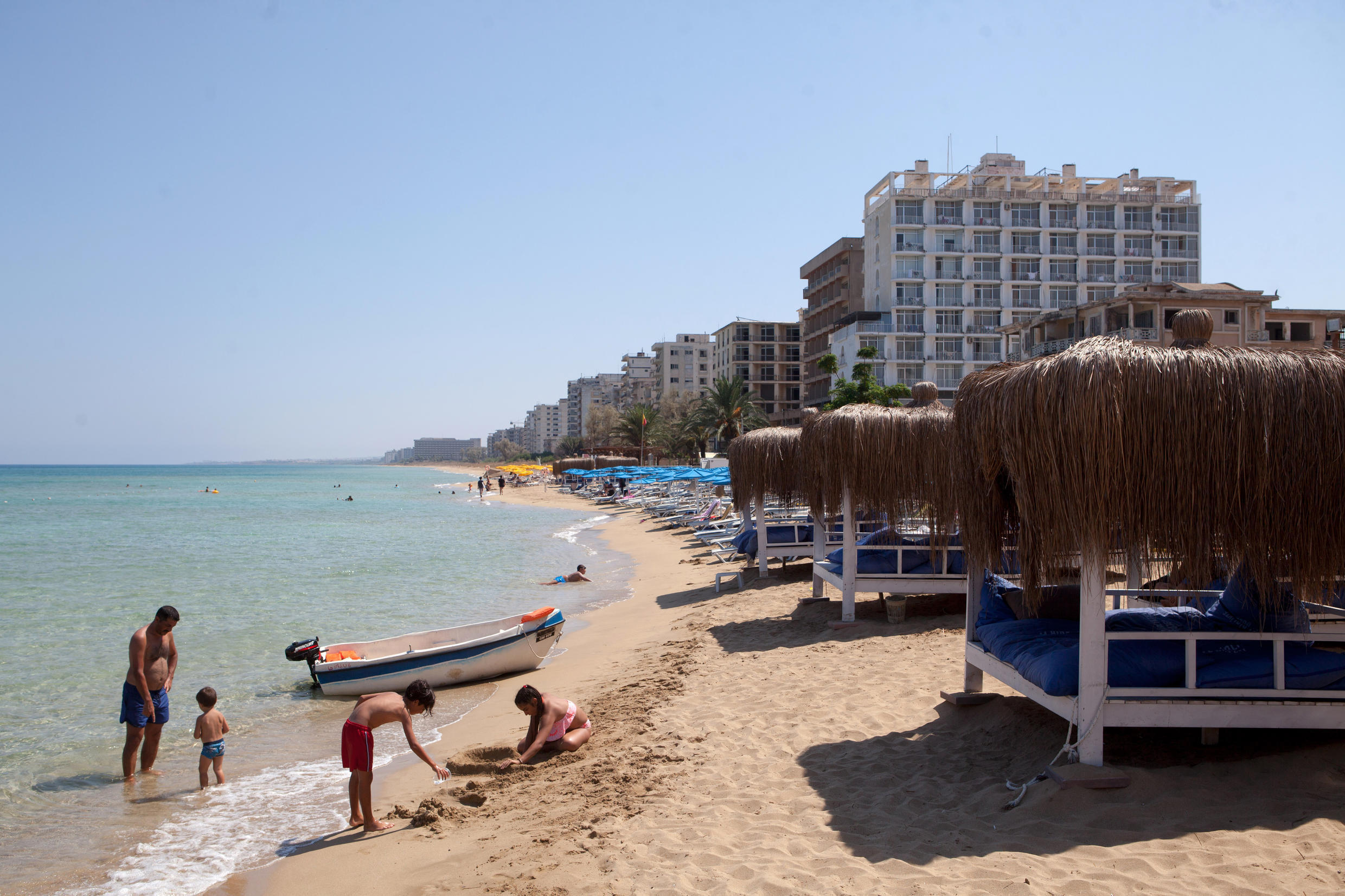 Tourists on a beach near the fenced-off beach area of the Turkish military-controlled ghost town of Varosha in northern Cyprus