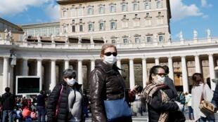 Turistas usam máscara de proteção durante visita à Cidade do Vaticano.