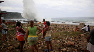 Gente observa olas en una playa de de Siboney antes de la llegada del huracán Matthew a Cuba.