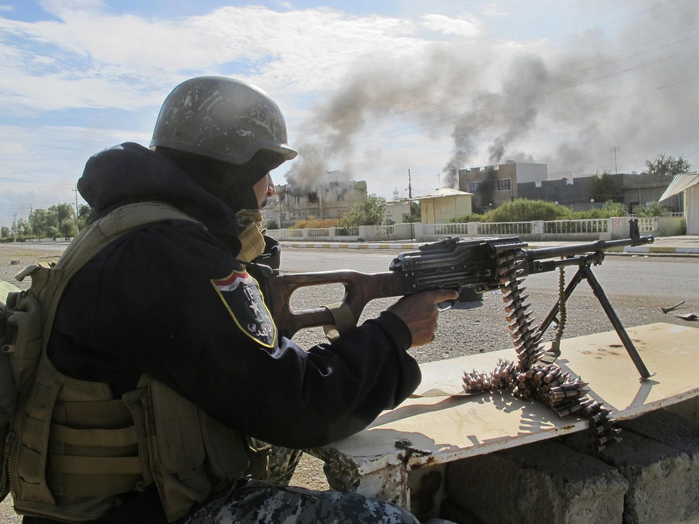 Un membre des forces de sécurité irakiennes tire sur une position islamiste, 115 km au nord de Bagdad, le 24 novembre 2014.