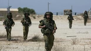 Israeli soldiers walk near the border with the central Gaza Strip July 14, 2014.