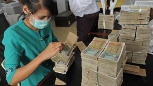 Une employée de la Banque de développement verte de l'Asie (AGD) compte des billets à Rangoon, le 10 janvier 2012.