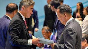 Một thành viên phái đoàn Mỹ trao cho ngoại trưởng Bắc Triều Tiên Ri Yong Ho (t) bức thư của tổng thống Mỹ trả lời thư của lãnh đạo Bình Nhưỡng Kim Jong Un, nhân hội nghị ASEAN ở Singapore ngày 04/08/2018.