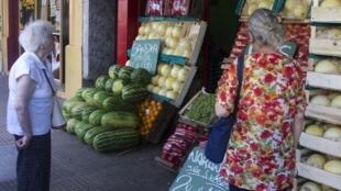 Clientas miran el precio de las verduras en un almacén de Buenos Aires.