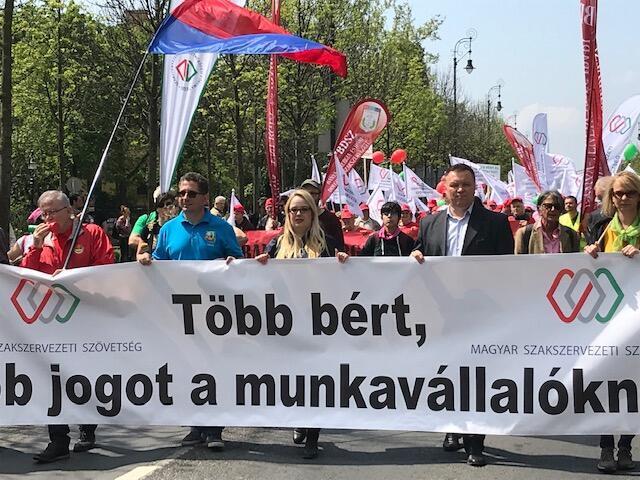 Trabalhadores carregam faixa por mais direitos sociais na manifestação do 1° de maio em Budapeste.